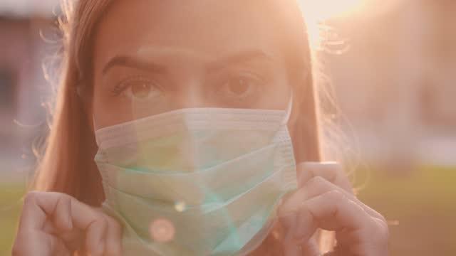 vídeos de stock e filmes b-roll de young woman showing you how to put on a protective face mask - calçada