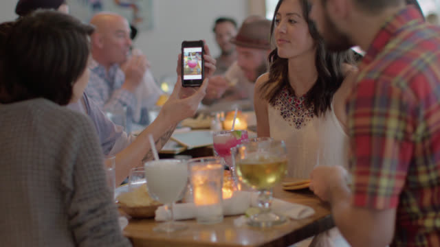 Young woman shows off photo to friends around table in restaurant