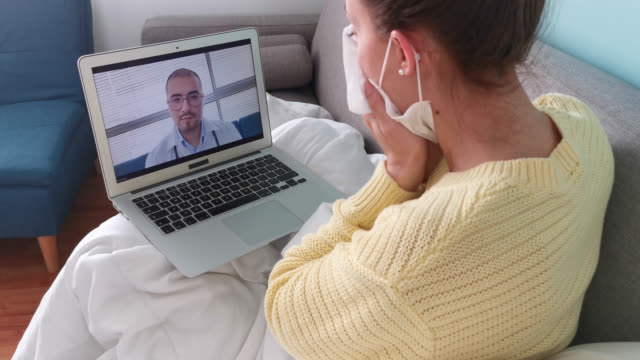 young woman sick at home during a telemedicine consult as doctor asks about her symptoms - mucus stock videos & royalty-free footage