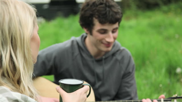vídeos de stock e filmes b-roll de young woman singing and young man playing guitar for friends outdoors - 20 24 anos