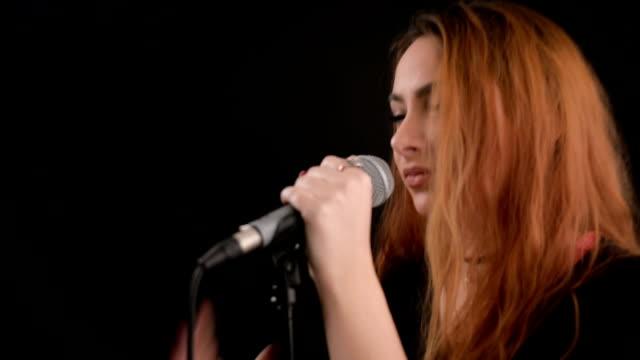 vídeos de stock, filmes e b-roll de jovem mulher cantando no microfone - cantora