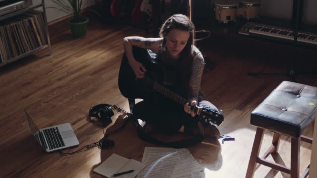 WS. Young woman sings and plays acoustic guitar with laptop and sheet music spread out on apartment floor.