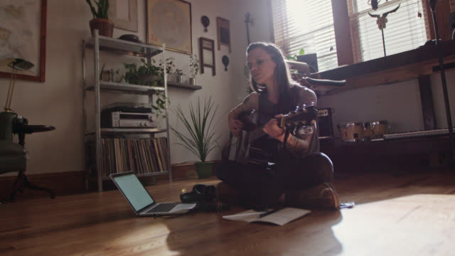 WS SLO MO. Young woman sings and plays acoustic guitar with laptop open on apartment floor.