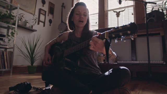 WS SLO MO. Young woman sings and plays acoustic guitar with sheet music spread out on apartment floor.