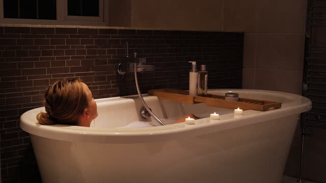 young woman sinking in to bath, relaxing - pampering stock videos & royalty-free footage