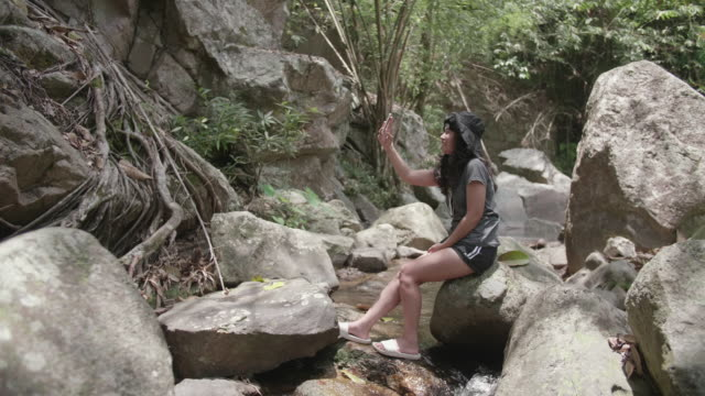 Young woman sit on rock posing for selfie near waterfall.