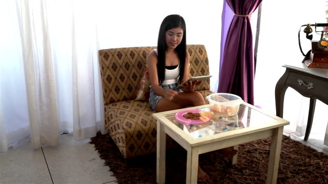 vídeos de stock, filmes e b-roll de jovem sentado no sofá usando tablet e comer lanches e frutas - reclinando