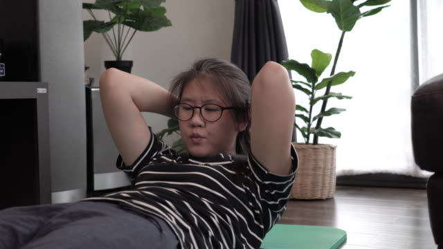 young woman sit ups at home during coronavirus covid-19 quarantine. - allenamento a corpo libero video stock e b–roll