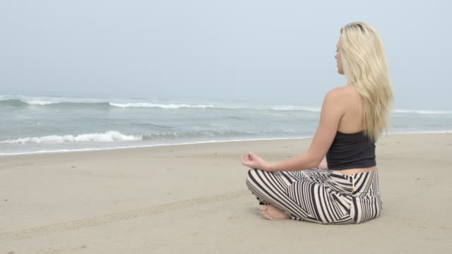 young woman sits and meditates on beach in malibu 4k - vesper stock stock videos & royalty-free footage