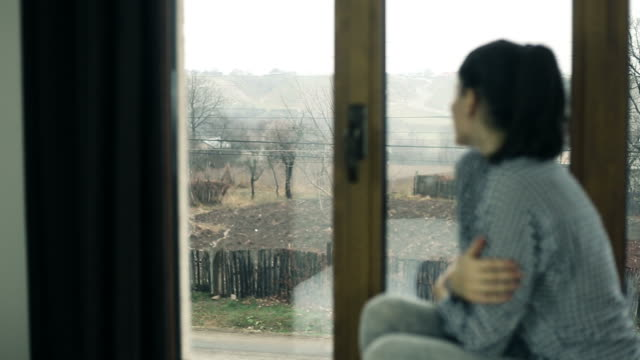 young woman sits by a window. - window frame stock videos and b-roll footage