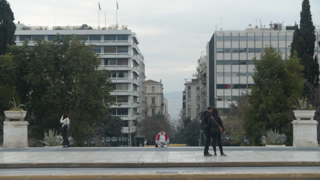 young woman sits in a yoga position at the syntagma square on the 22nd of march 2020, a few hours before a complete lockdown takes place in greece... - 災害対策点の映像素材/bロール