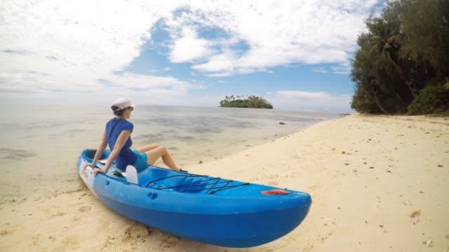 young woman sits on a kayak enjoys muri lagoon in rarotonga, cook islands - rarotonga stock videos & royalty-free footage