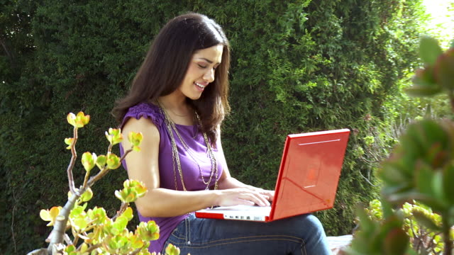 ms zi young woman sits on garden wall and using laptop / sherman oaks, california, usa. - see other clips from this shoot 1655 stock videos & royalty-free footage