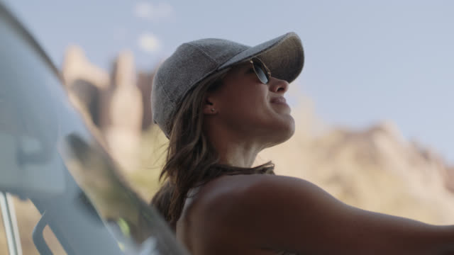 young woman sits on hood of car and looks up at moab campground. - bonnet stock videos & royalty-free footage