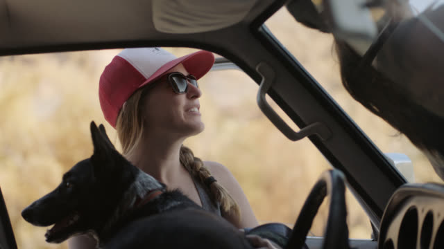 young woman sits on hood of car and talks with friend on moab camping trip. - on the move stock videos & royalty-free footage