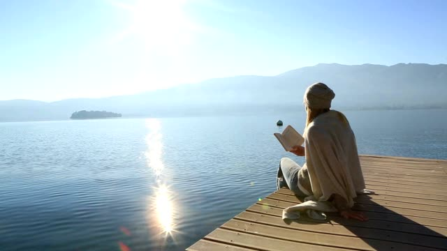 young woman sits on jetty above lake, reading book - serene people stock videos & royalty-free footage