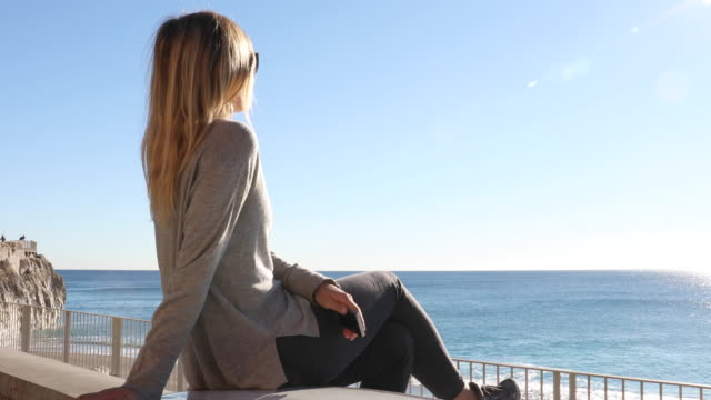 young woman sits on stone wall, looks out to sea - woman taking clothes off stock videos and b-roll footage