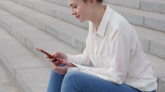 vídeos de stock e filmes b-roll de young woman sits on the steps with smartphone - blusa