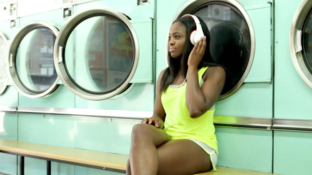 mls a young woman sits waiting in a launderette - waschsalon stock-videos und b-roll-filmmaterial
