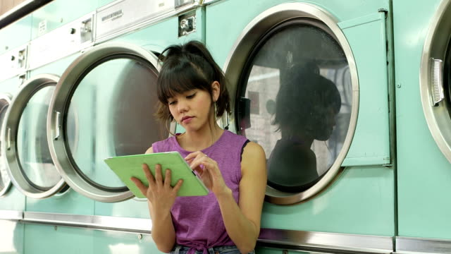 ms a young woman sits waiting in a launderette - launderette stock videos & royalty-free footage