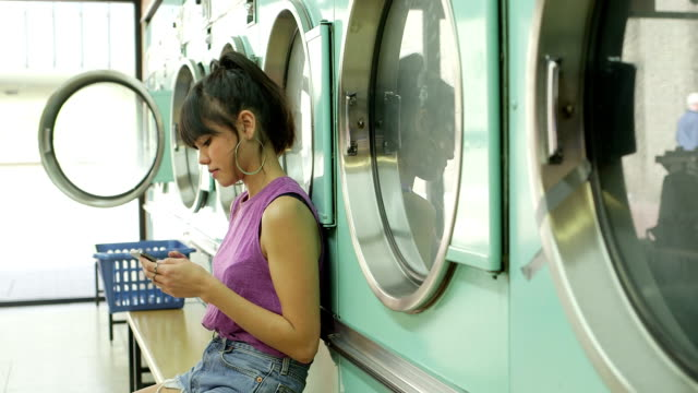 ms a young woman sits with her smartphone in a launderette - wäschekorb stock-videos und b-roll-filmmaterial