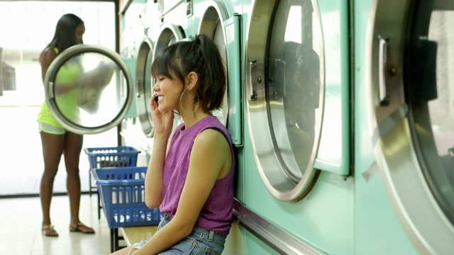 a young woman sits with her smartphone in a launderette - 輪っかのイヤリング点の映像素材/bロール
