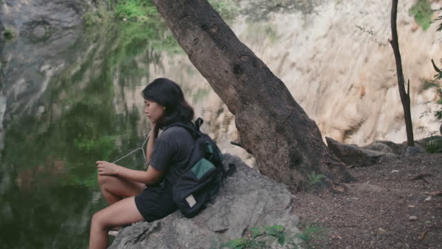 young woman sitting and listening to music at river's edge, mountains. - bag stock videos & royalty-free footage