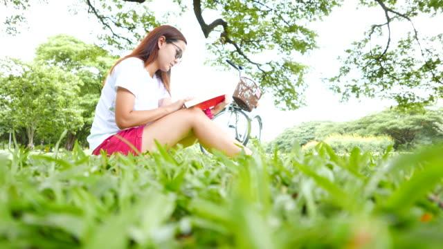 Junge Frau sitzen und lesen ein Buch im Park
