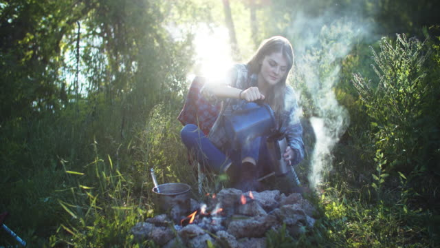 young woman sitting around a campfire - drinking stock videos & royalty-free footage
