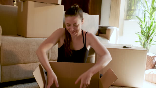young woman sitting arranging moving home. - cushion stock videos & royalty-free footage