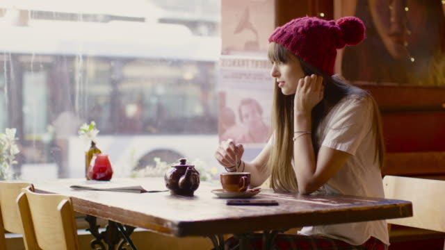 a young woman sitting at a table in a coffee shop in manchester - technophile stock videos & royalty-free footage