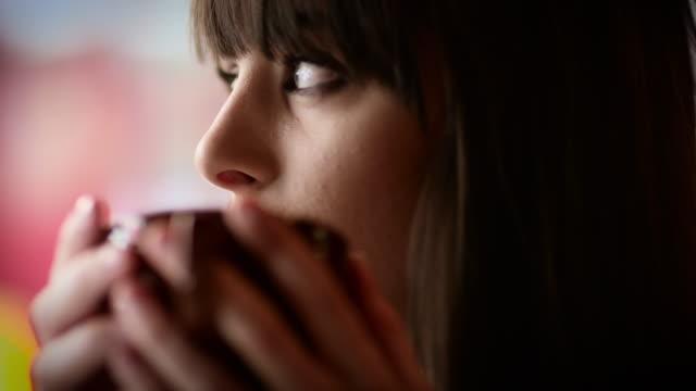 vídeos y material grabado en eventos de stock de a young woman sitting at a table in a coffee shop in manchester - taza