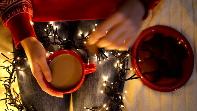 junge frau sitzt zu hause auf dem boden neben dem weihnachtsbaum. halten sie eine tasse kaffee und isst kekse - keks stock-videos und b-roll-filmmaterial
