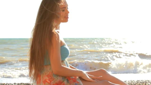 HD Young woman sitting at sea beach