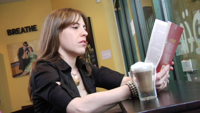 ms young woman sitting at table in coffee shop and reading a book/ vancouver, bc - kelly mason videos 個影片檔及 b 捲影像