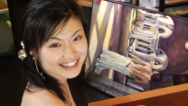 vídeos y material grabado en eventos de stock de ms portrait young woman sitting at table in coffee shop painting behind her/ vancouver, bc - kelly mason videos