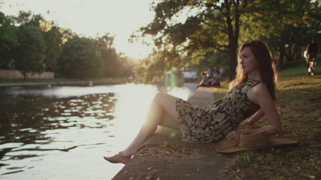 Young woman sitting by river in summer