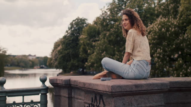 young woman sitting by spree river in berlin eating blueberries smiling - スプリー川点の映像素材/bロール