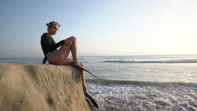 stockvideo's en b-roll-footage met ws young woman sitting by the sea getting ready to snorkel - zwemvlies