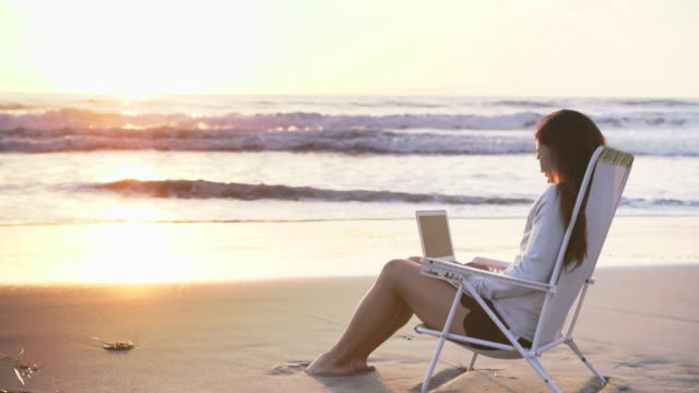 ws young woman sitting by the sea working on a laptop at sunset. - serene people stock-videos und b-roll-filmmaterial