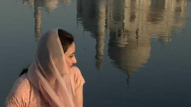 cu, young woman sitting by water reflecting taj mahal, agra, uttar pradesh, india - mughal empire stock videos and b-roll footage