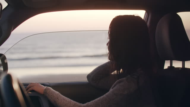 vidéos et rushes de young woman sitting in a car by the beach - stationary