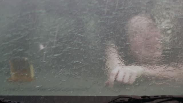 Young woman sitting in a car in rain season, Delhi, India