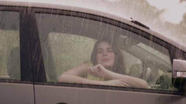 vidéos et rushes de young woman sitting in a car in rain season, delhi, india - fondu d'ouverture
