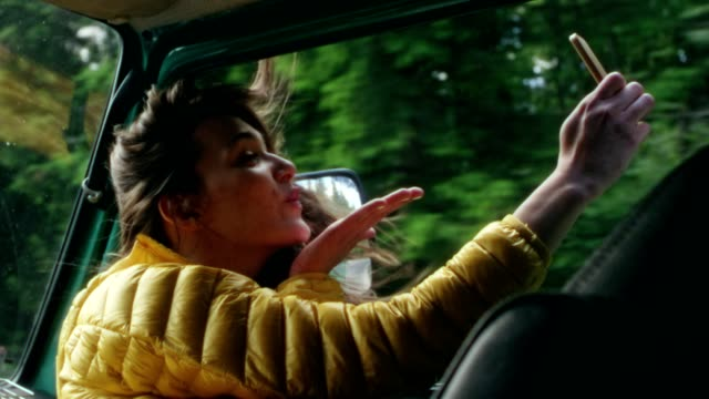 Young woman sitting in a van. Blowing a kiss for a selfie