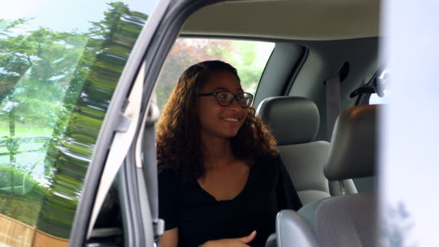 ms young woman sitting in back of car holding smartphone in discussion with passengers - back seat stock videos and b-roll footage