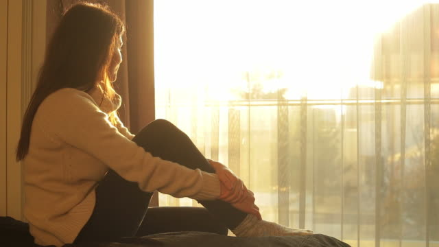 young woman sitting in bed admiring the sunlight. - mid adult stock videos & royalty-free footage