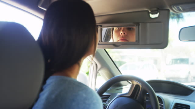 young woman sitting in car checking her makeup in mirror - examining stock videos & royalty-free footage