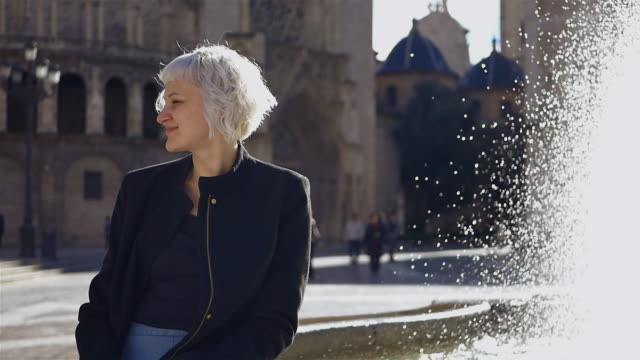 young woman sitting in front of fountain in old town of valencia - mittellanges haar stock-videos und b-roll-filmmaterial