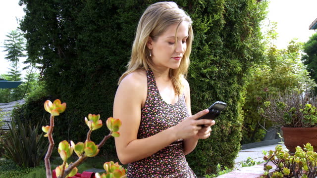 ms pan young woman sitting in garden text messaging on her smart phone / sherman oaks, california, usa.  - see other clips from this shoot 1655 stock videos & royalty-free footage